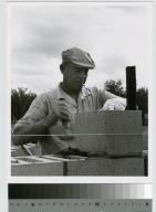 Construction worker lays concrete block