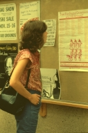 Female student reads posters on bulletin board in the SAU