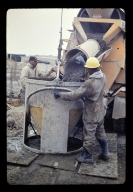 Two construction workers pour cement