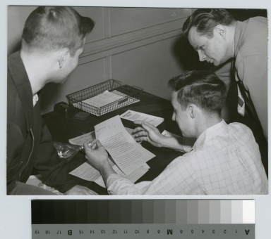 Student activities, three RIT reporter staff members reading a document