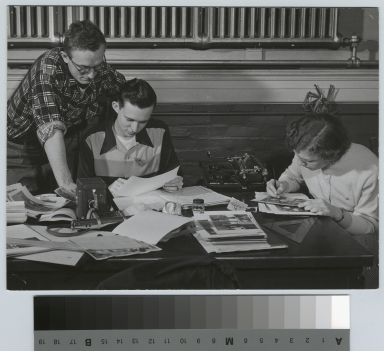 Student activities, three RIT Reporter staff members working on a newspaper story