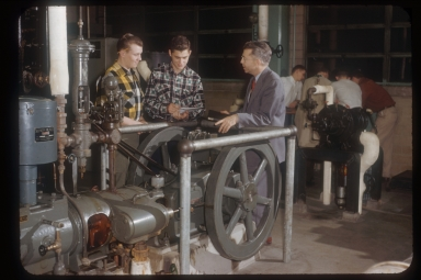 Two students and instructor talk by machinery, Rochester Institute of Technology