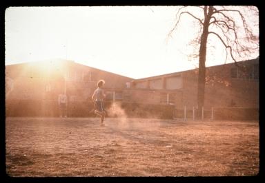 Unidentified person runs in a dusty yard