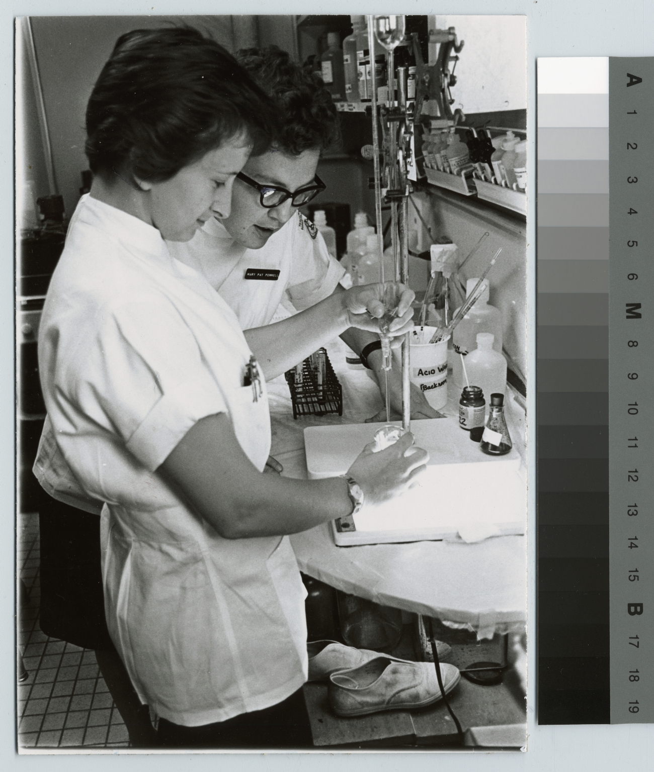 Academics, biology, two medical technology students performing an experiment, [1950-1968]