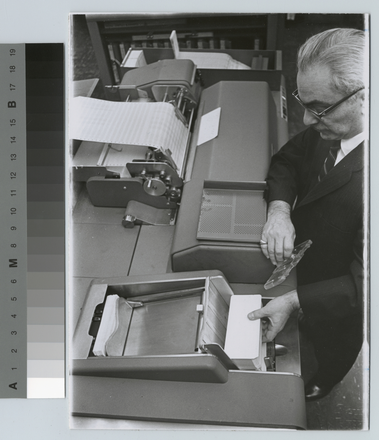 Academics, computer science, Rochester Institute of Technology data processing instructor loading punch cards into a computer, [1968-1980]