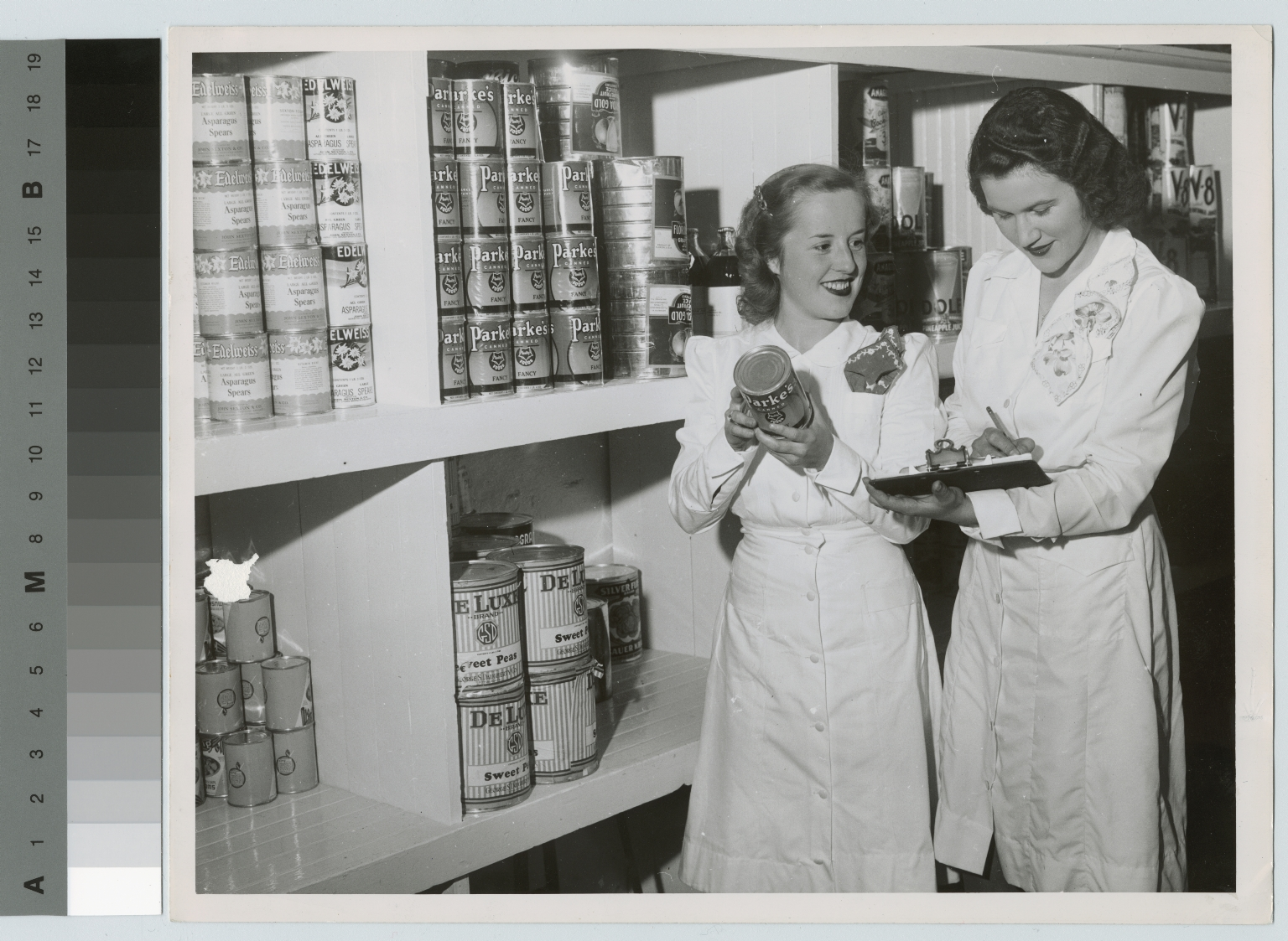 Academics, two unidentified students in Food Administration examining cans, [1949-1950]
