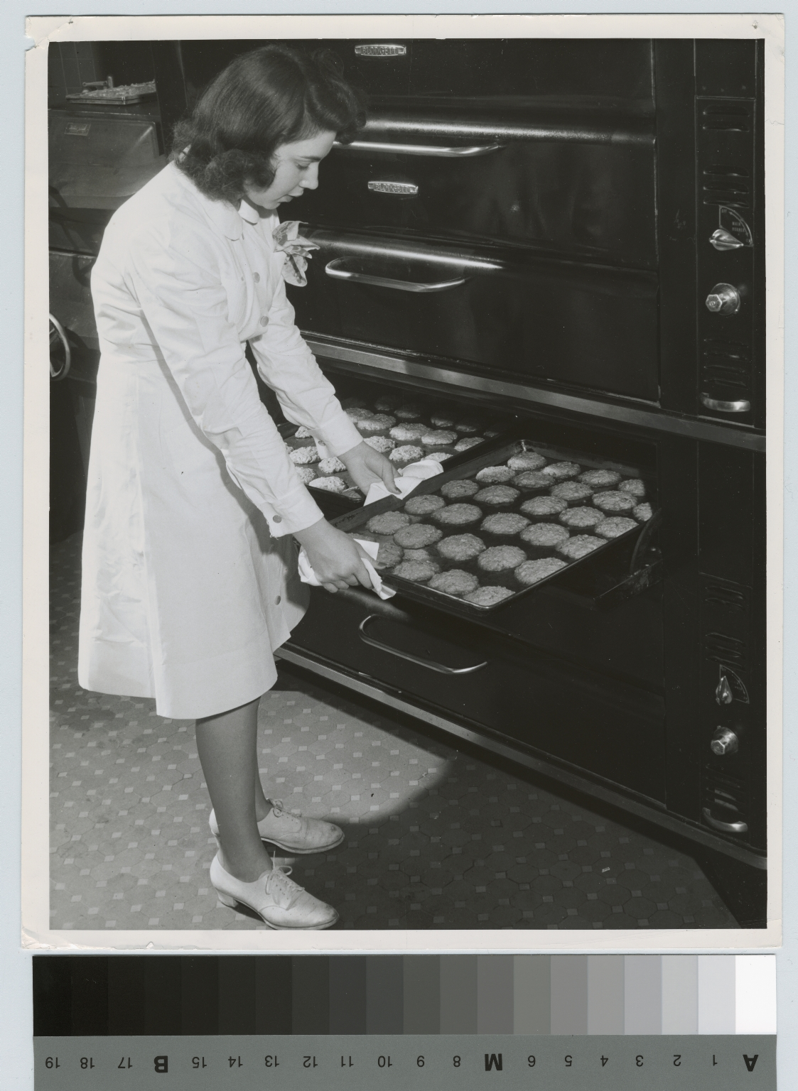 Academics, Food Administration student, Marian Kaufman, removing cookie sheet from oven, 1942.