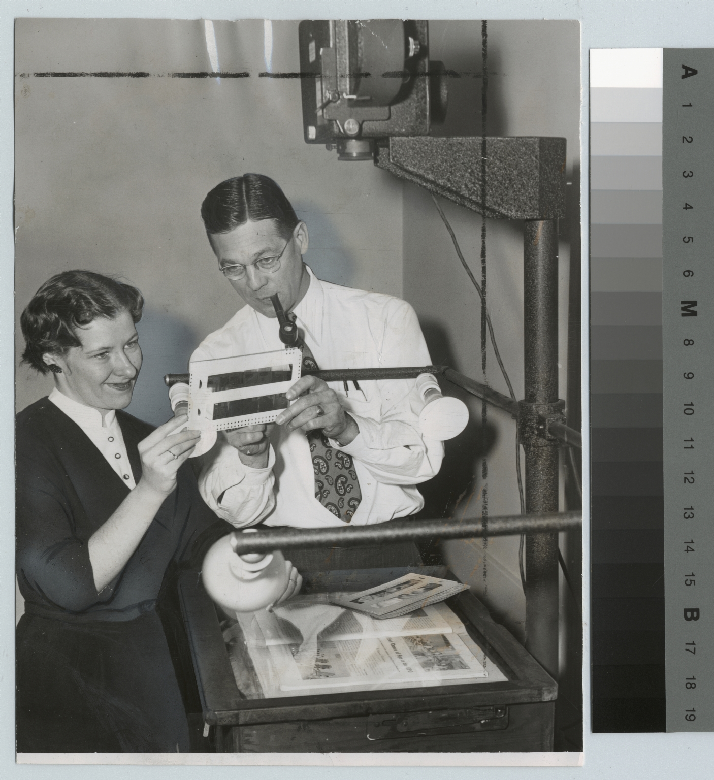 Examiniing slide in Graphic Arts Research Department, Rochester Institute of Technology [1954]