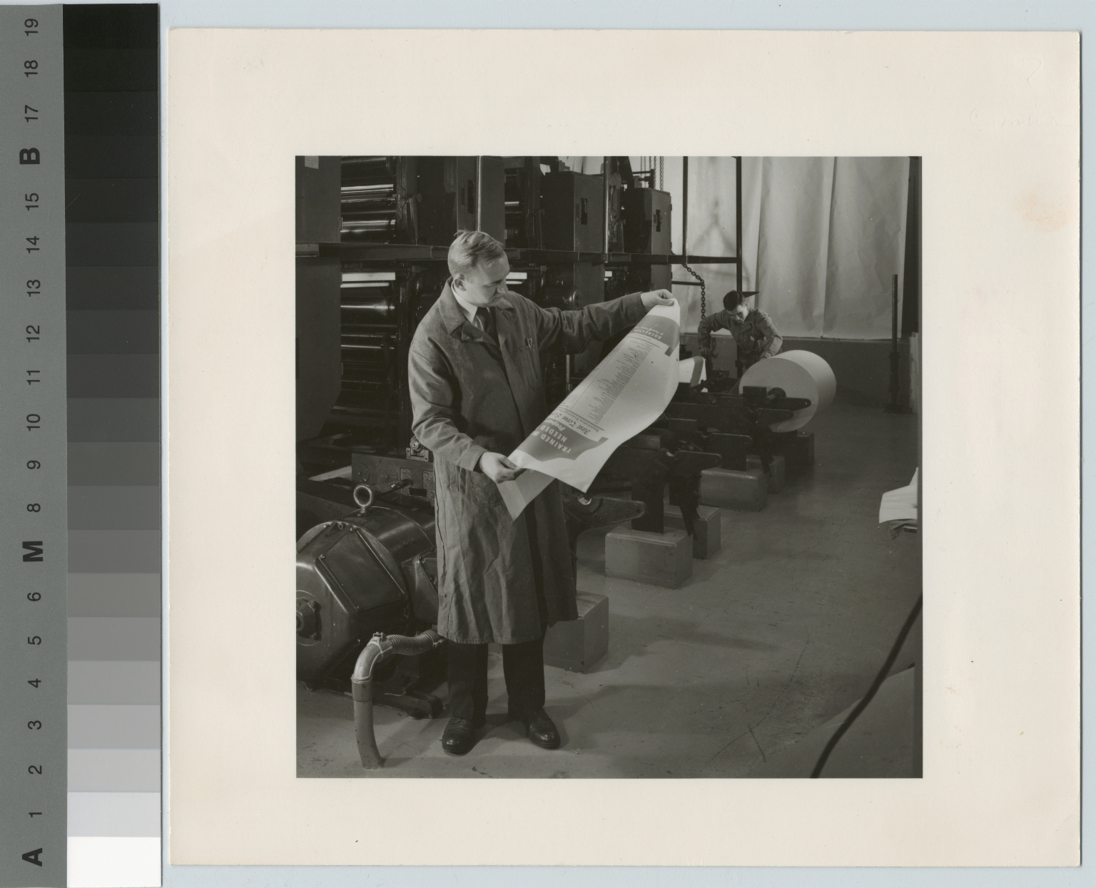 Technician examining poster from printing press, Rochester Institute of Technology, [1950-1959]