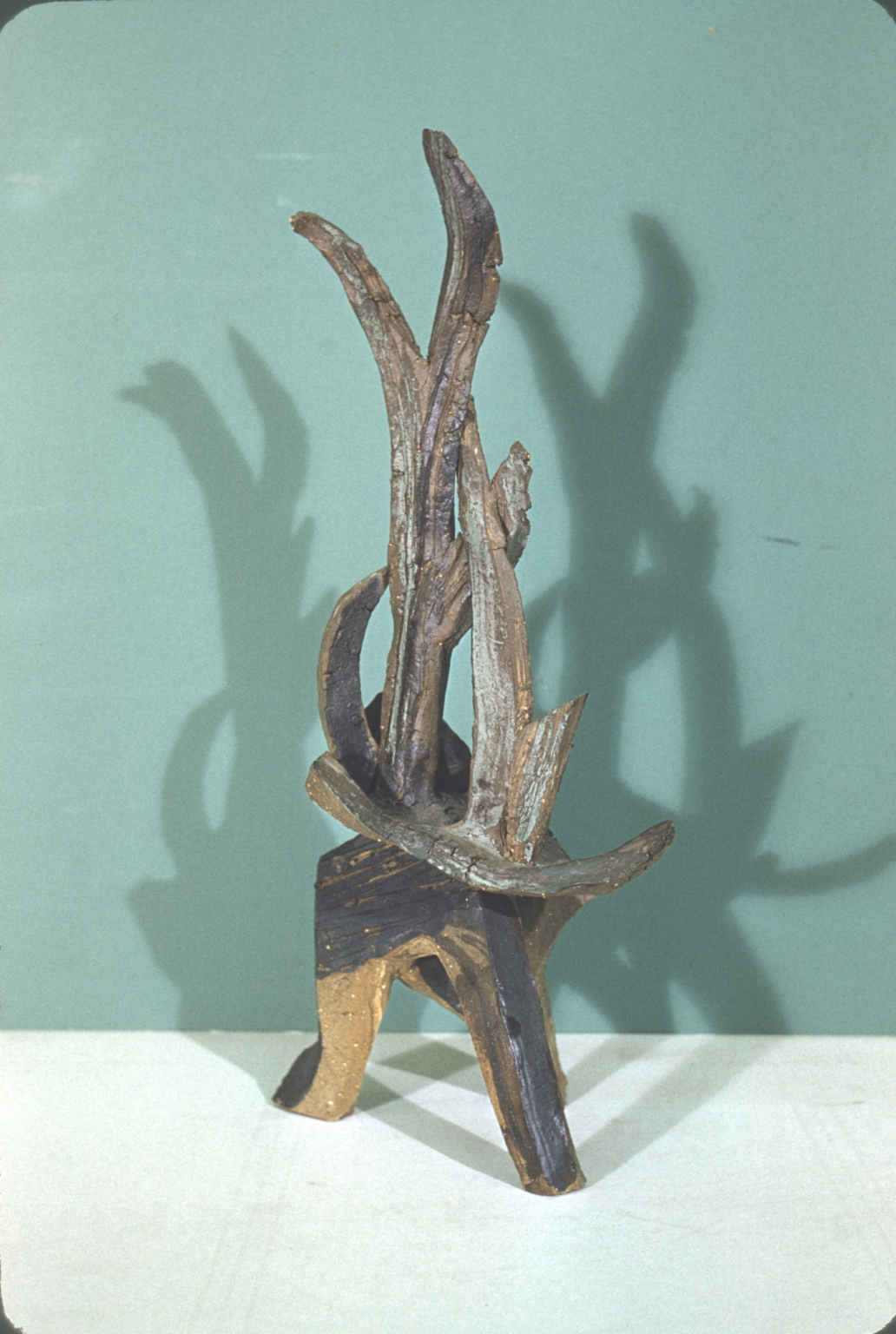 Ceramic sculpture shown over a white table with a blue background