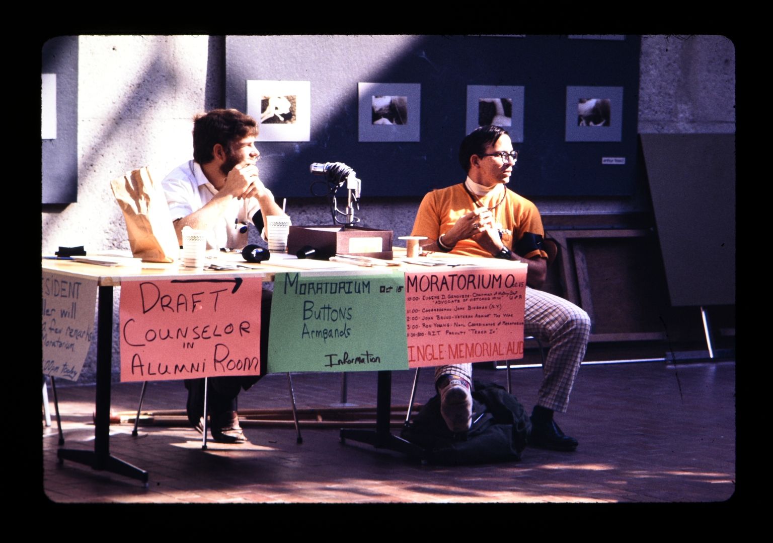 Two unidentified students sit at a table in the Student Alumni Union promoting the Moratorium
